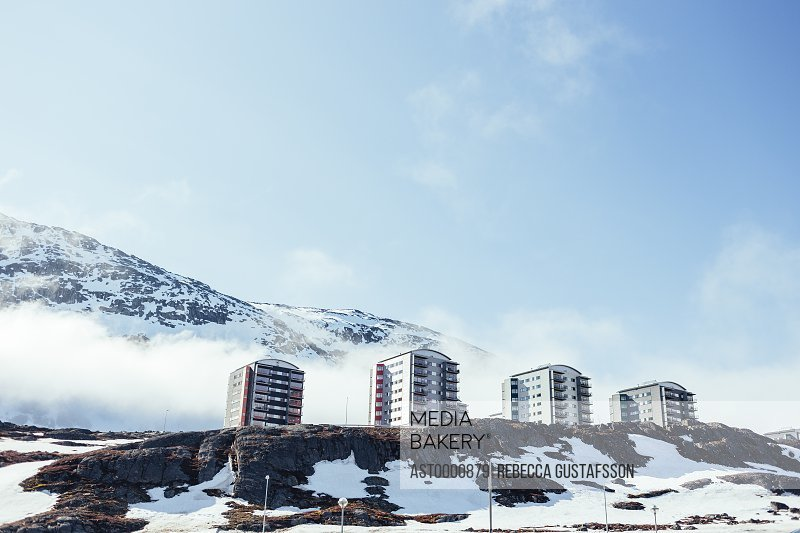 Low angle view of apartment buildings on snow covered mountain against sky