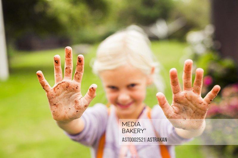 Portrait of girl showing her dirty hands in garden