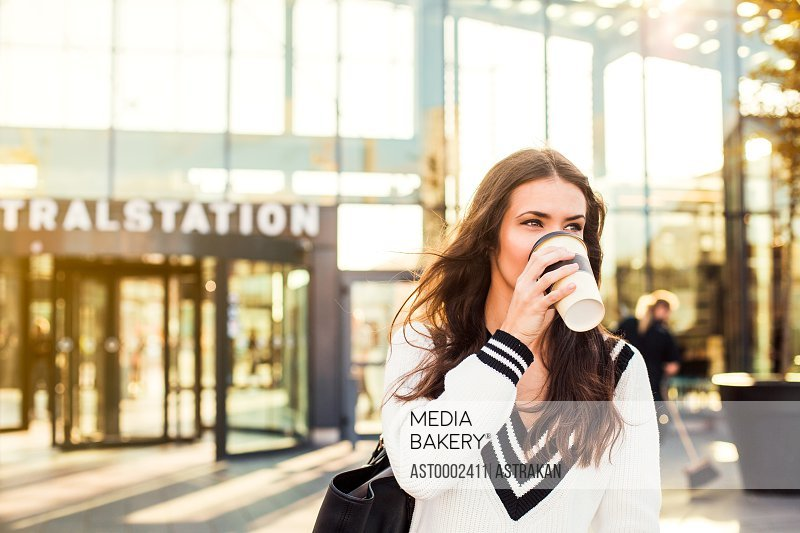 Businesswoman drinking coffee from disposable cup outside railroad station