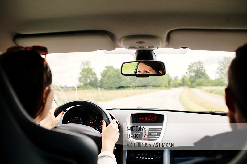 Cropped image of young woman driving car