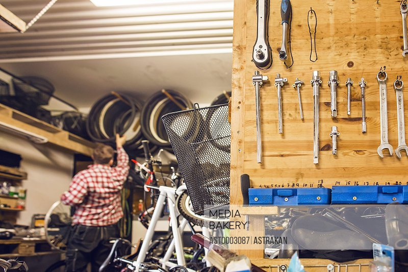 Rear view of man working in bicycle shop