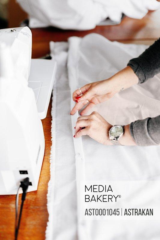 Cropped hands of fashion designer pinning white textile at studio