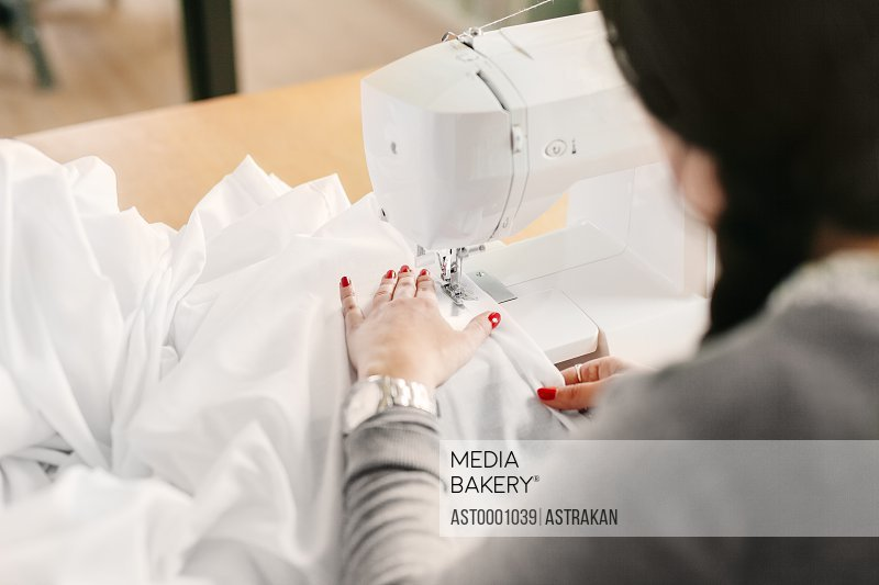 High angle view of female designer using sewing machine at studio