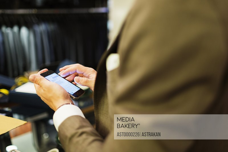 Midsection of salesman using smart phone in clothing store