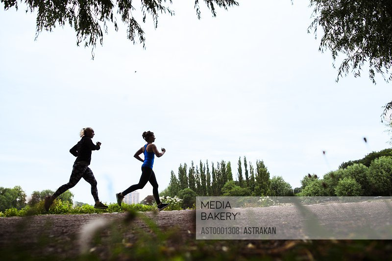 Side view of determined women jogging at park against sky