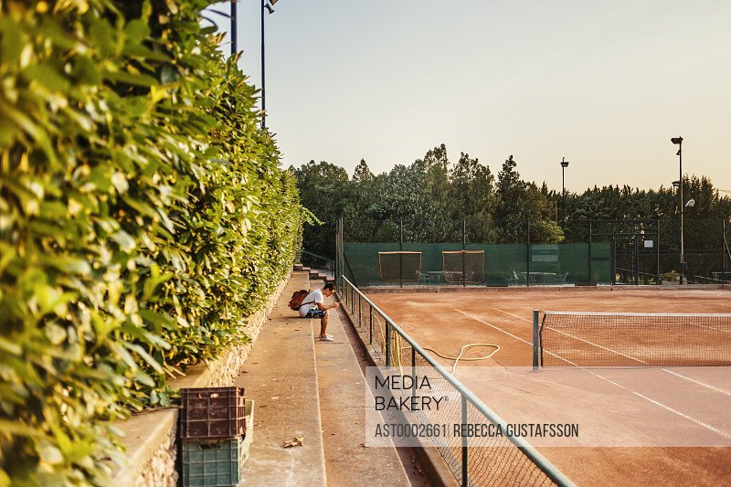 Young man sitting on steps at tennis court