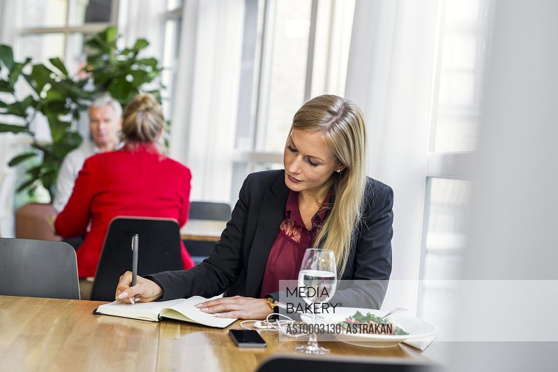 Businesswoman writing in book at table in restaurant