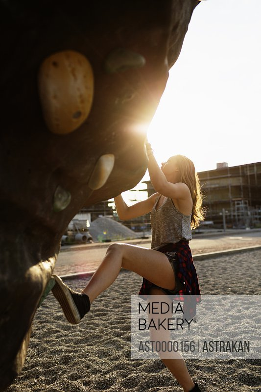 Side view of sporty teenage girl climbing up artificial rock