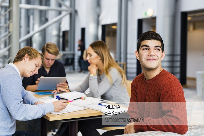 Thoughtful young male student sitting with friends studying in university