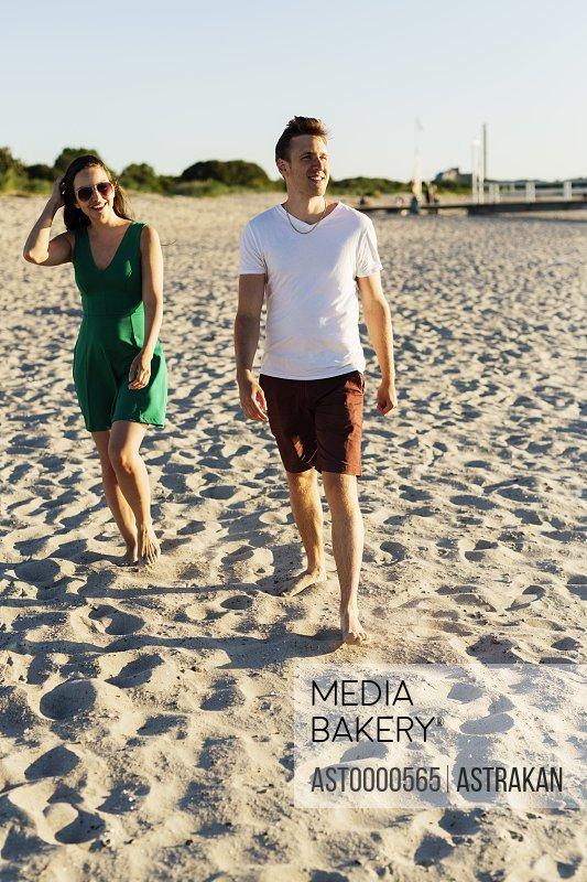 Couple walking on sand at beach