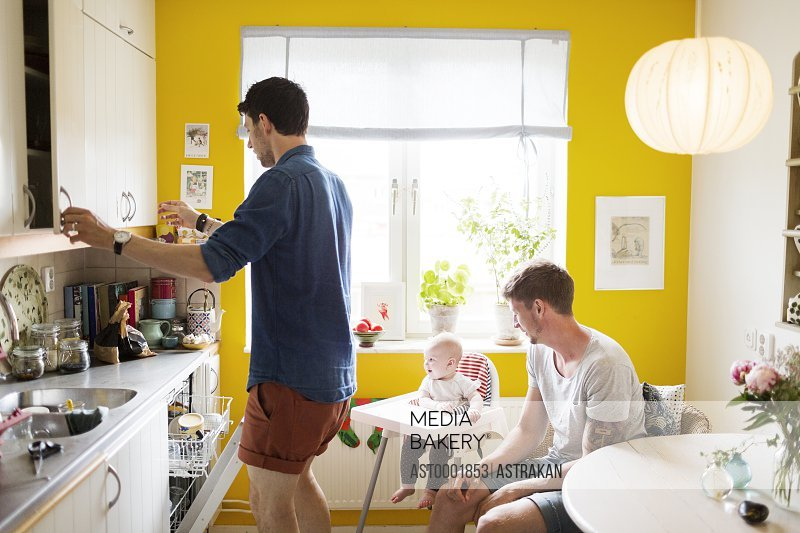 Gay couple with baby girl sitting on high chair in kitchen