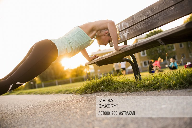 Side view of determined woman doing push-ups on wooden bench at park