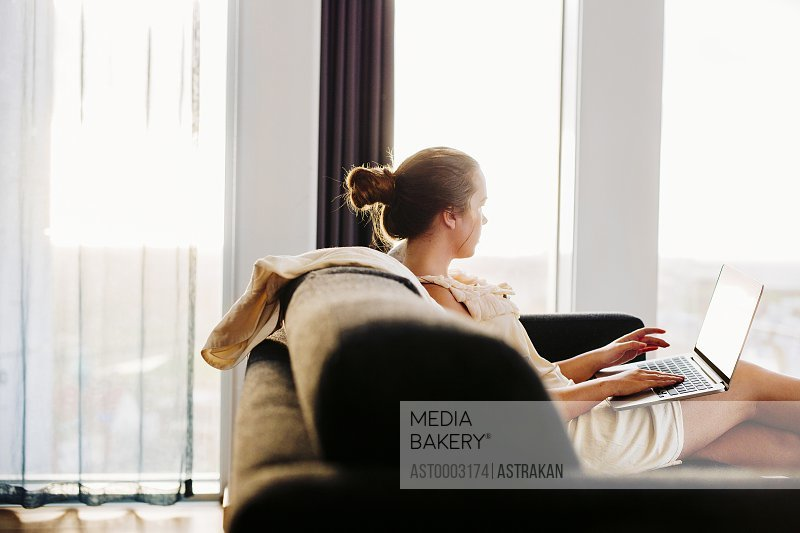 Businesswoman using laptop while relaxing on sofa at hotel room