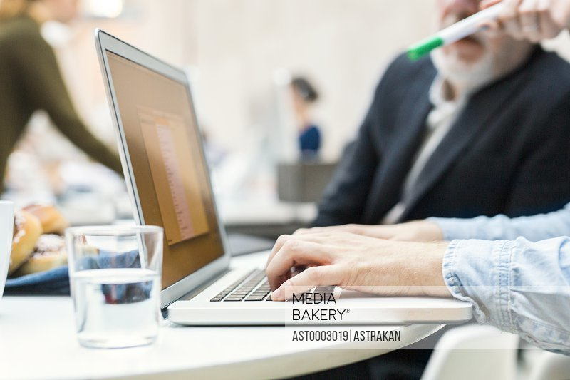 Cropped image of business people discussing project on laptop in office