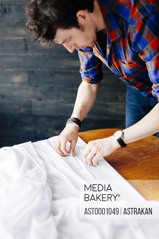 Male fashion designer pinning white textile at table in studio