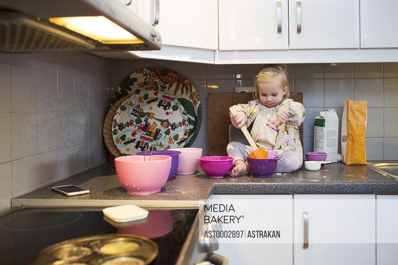 Cute girl preparing pancake while sitting on kitchen counter