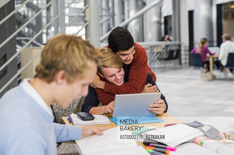Young male student embracing friend from behind at university