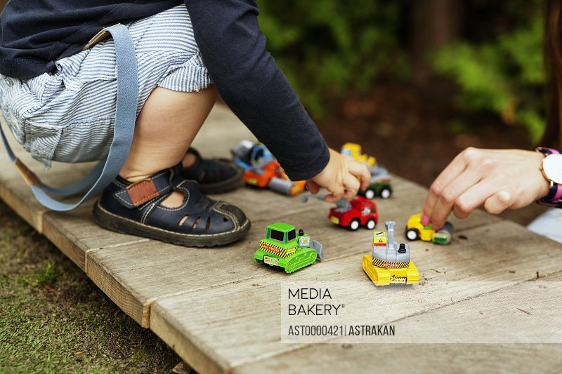 Cropped image of boy and mother playing with toy cars in park