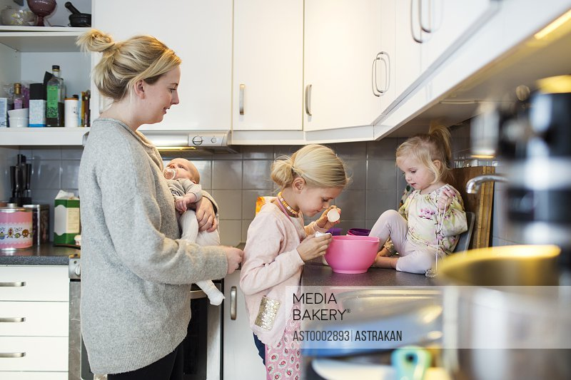 Family preparing pancake in domestic kitchen