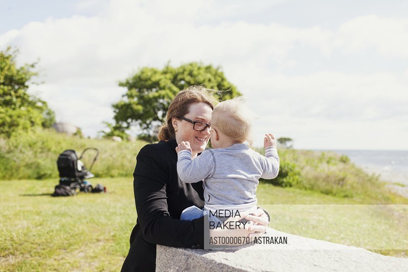 Happy mother with son on grassy field