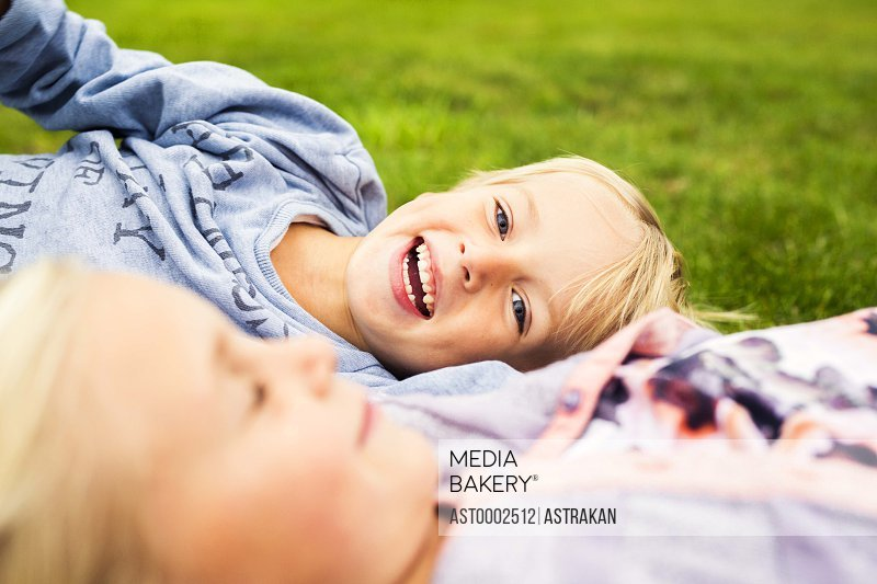 Portrait of cheerful boy with sister relaxing in yard