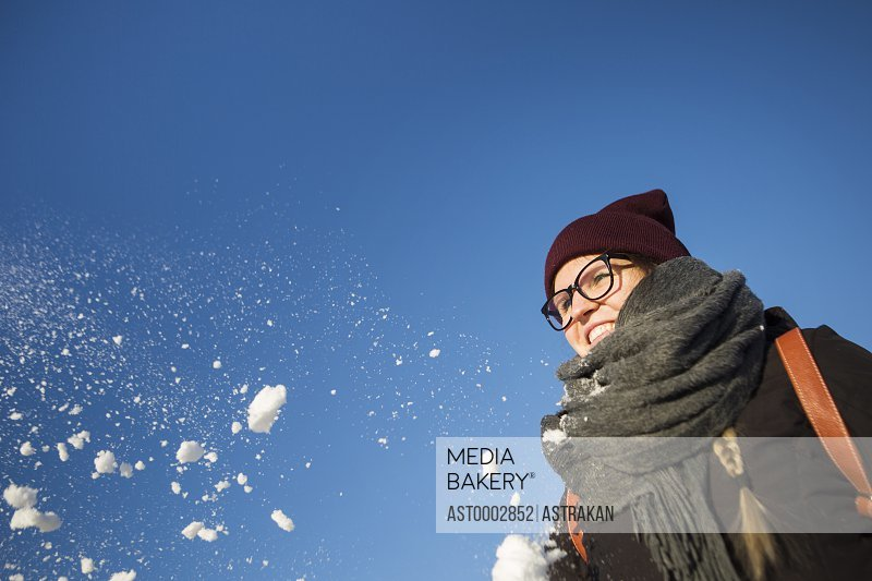 Low angle view of happy woman playing with snow against clear blue sky
