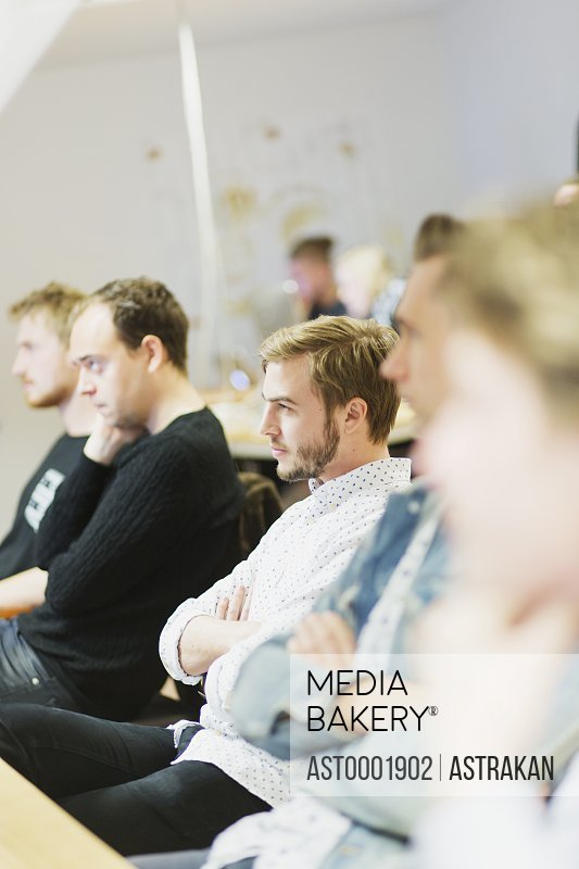Male students sitting in media class