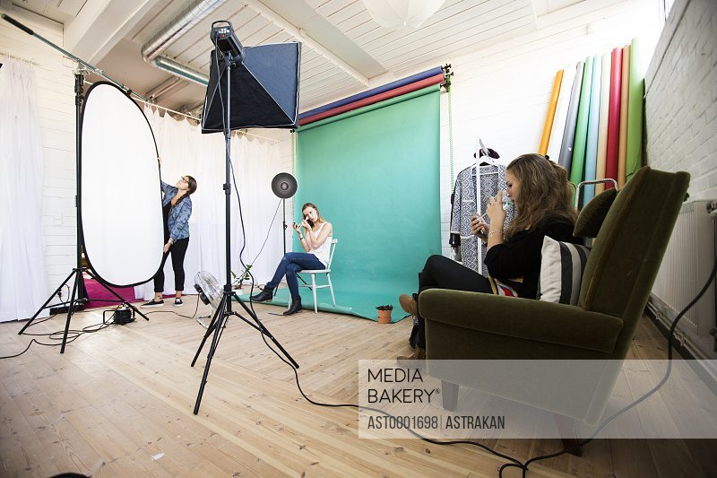 Fashion models getting dressed while assistant working in photo studio