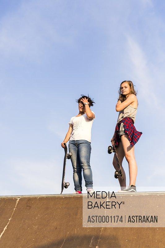 Full length of female friends with skateboards in skate park