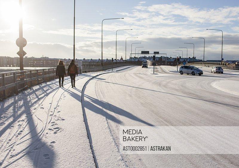 Rear view of women walking on snow covered sidewalk in city