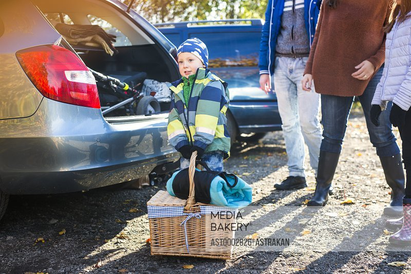 Little boy trying to pick up picnic basket by family and car in countryside