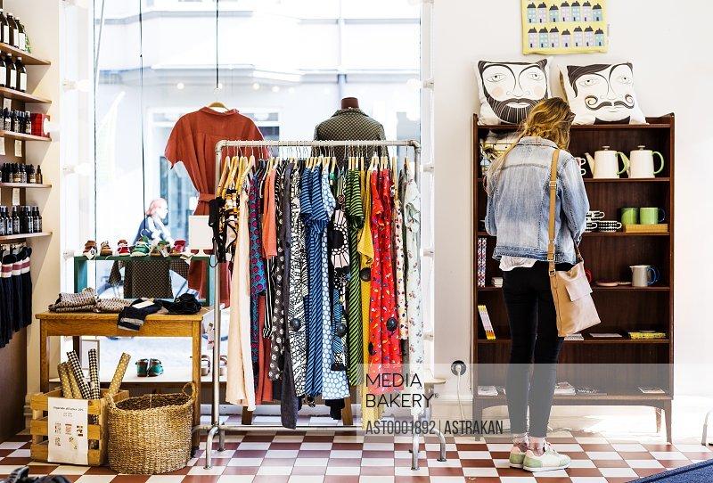 Rear view of woman shopping crockery in store
