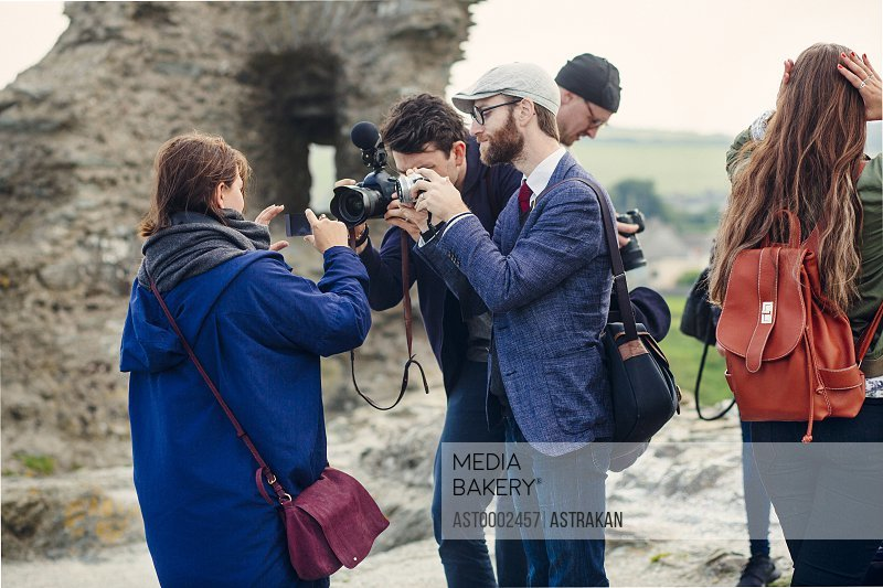 Men photographing woman holding smart phone at beach