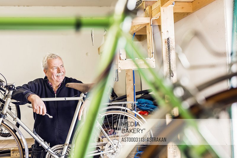 Thoughtful senior repairman leaning on bicycle in workshop