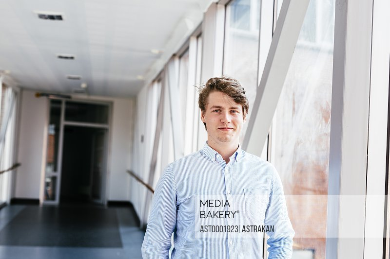 Portrait of confident male media student standing at passage in university