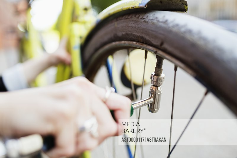 Cropped image of woman's hand inflating bicycle tire on sidewalk