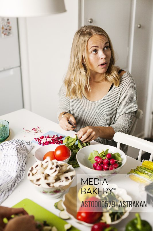 Young woman looking away while cutting vegetables in kitchen