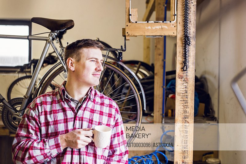 Thoughtful repairman holding coffee mug while looking away at workshop
