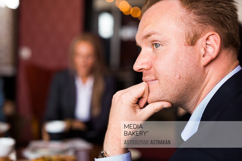 Side view of thoughtful businessman with hand on chin in office
