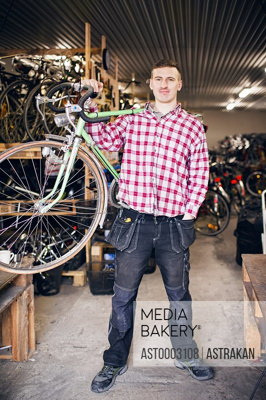 Full length portrait of owner carrying bicycle in workshop