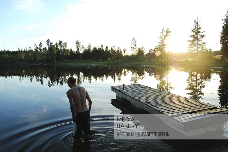 Rear view of young man wading in lake at sunset