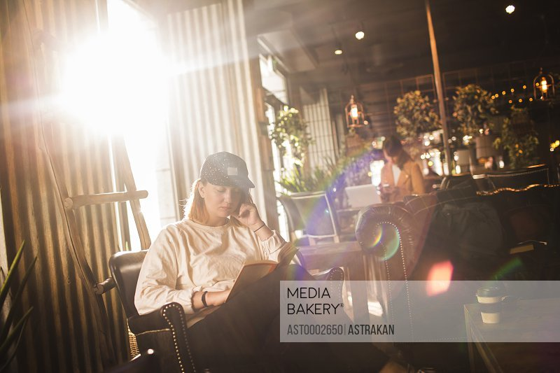 Woman reading book in bright cafe