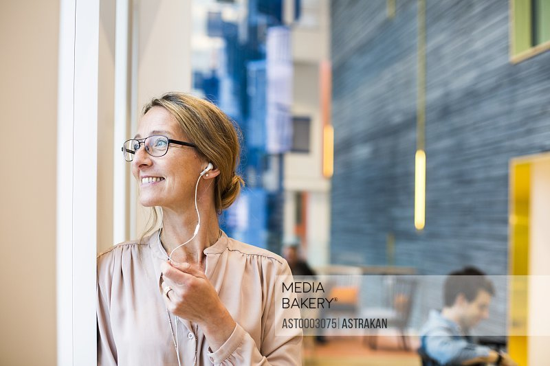 Happy businesswoman looking through window while listening music at hotel lobby