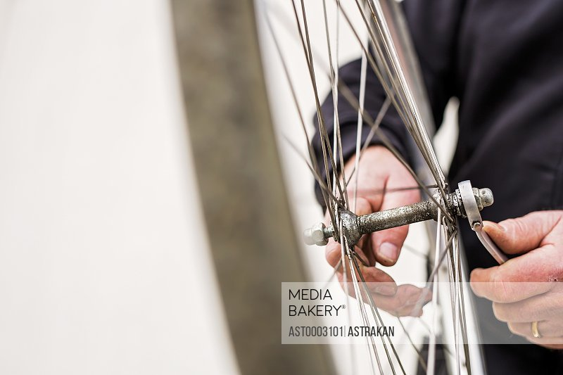 Midsection of senior man tightening bicycle tire outside workshop
