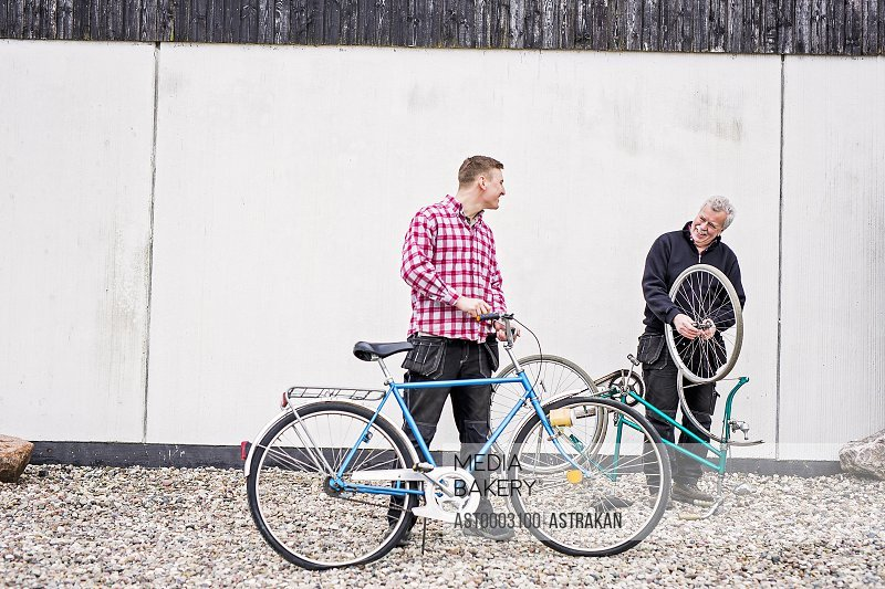 Full length of happy father and son talking while repairing bicycles outside workshop