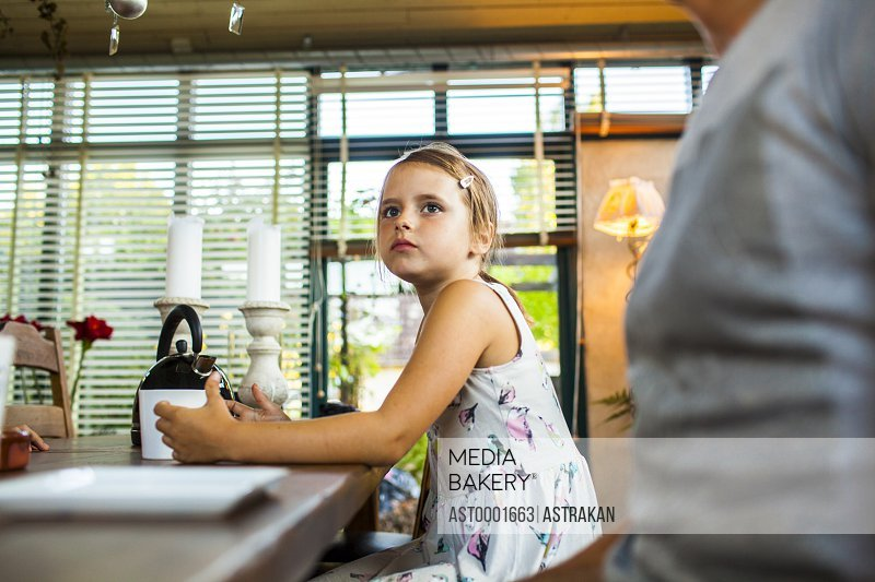 Girl sitting beside father at breakfast table