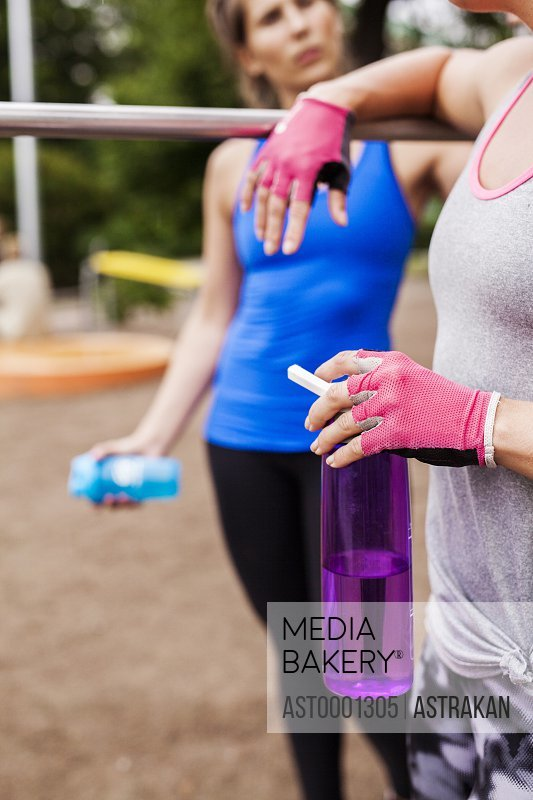 Midsection of sporty woman holding water bottle while standing friend at park