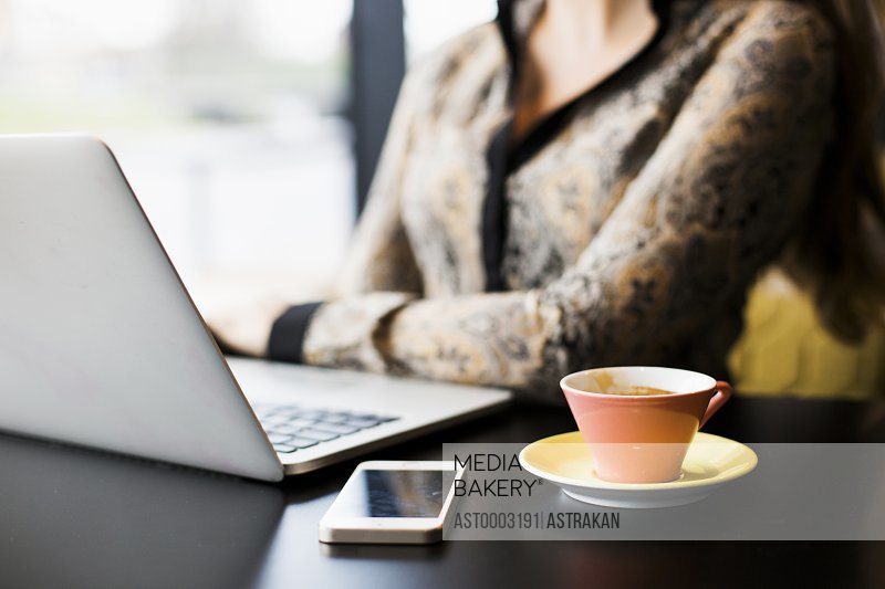 Midsection of woman with laptop and smart phone by coffee cup at table