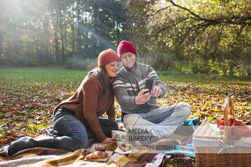 Happy mature couple taking selfie through mobile phone in forest during picnic