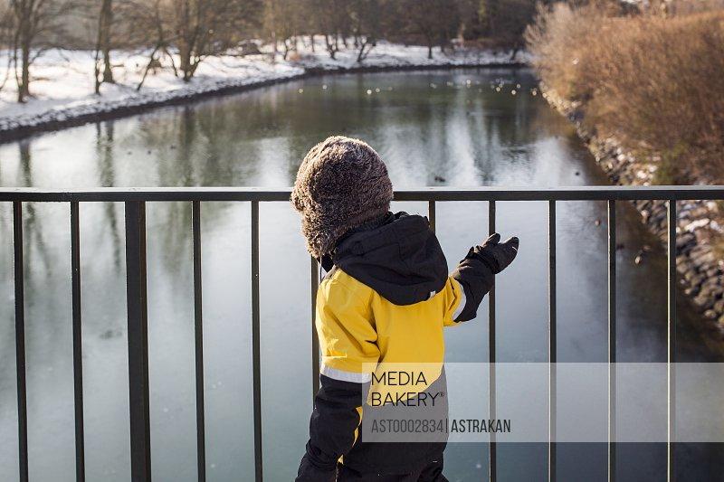 Boy walking by bridge railing over river during winter